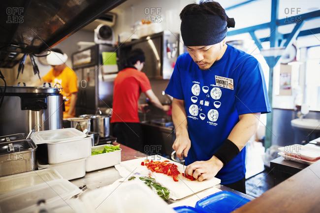 Japan - July 25, 2015: Ramen noodle shop. Three chefs working in a small kitchen, staff preparing food