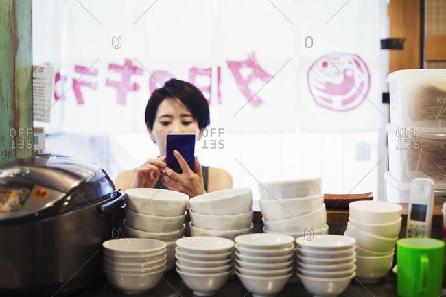 A woman using a smart phone at a noodle shop.