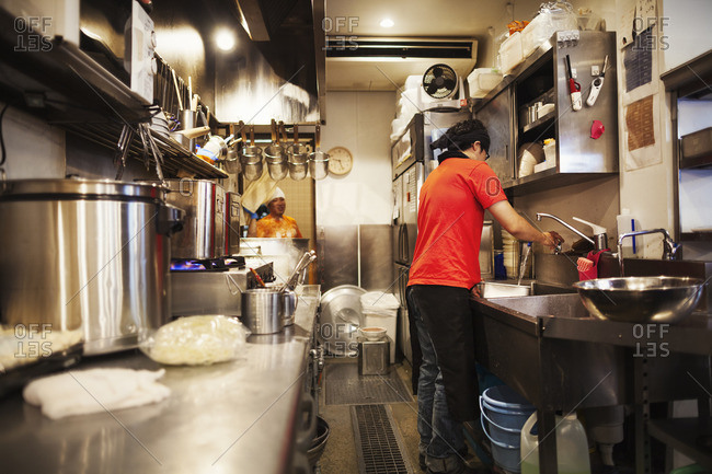 Ramen noodle shop. A chef working in a kitchen preparing food using a stove and large pans.