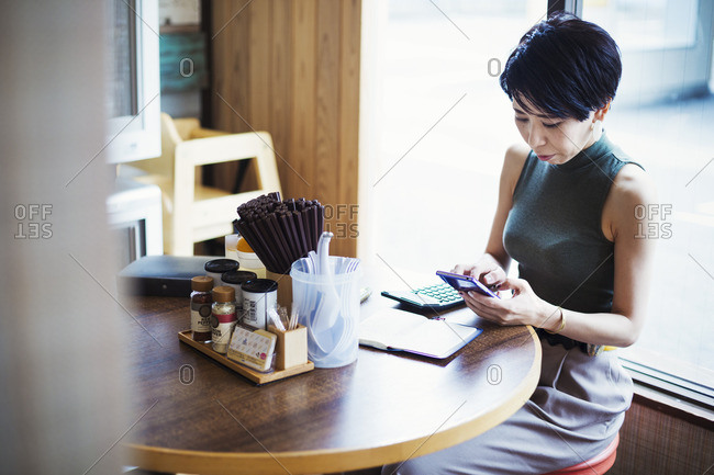 Ramen noodle shop. A woman sitting at a table using her smart phone.