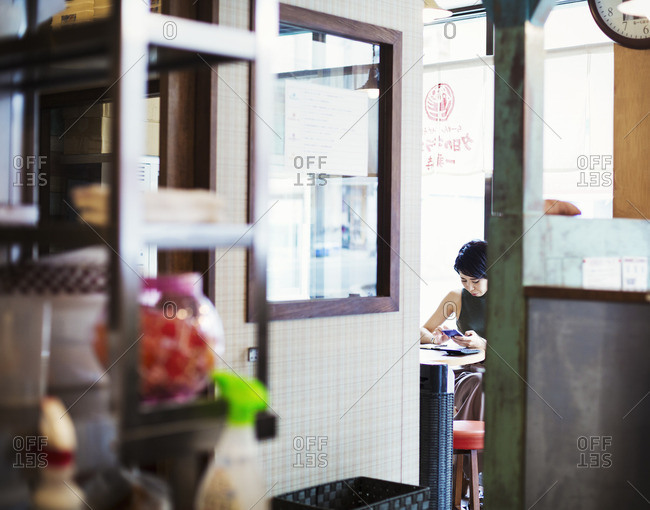Ramen noodle shop. A woman sitting in a cafe, view through a door.