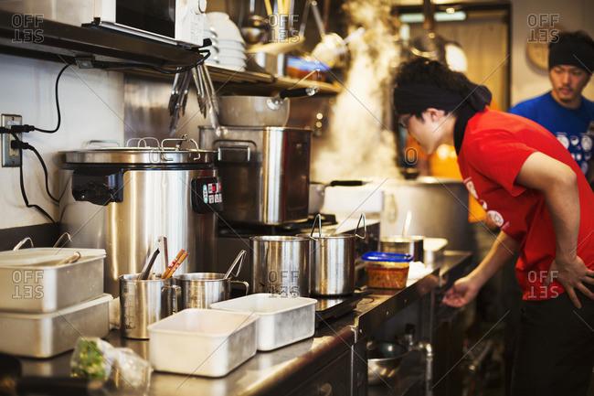 Ramen noodle shop.  Staff preparing food in a tiny kitchen