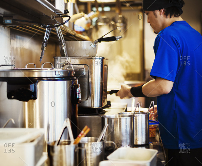 Ramen noodle shop. A chef working in a kitchen.