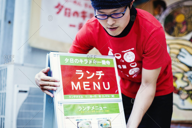 Japan - July 25, 2016: Ramen noodle shop. A man putting out the advertising board and menu on the sidewalk.
