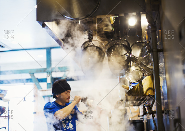Ramen noodle shop. A chef working in a kitchen with steam rising from the pots of noodles.