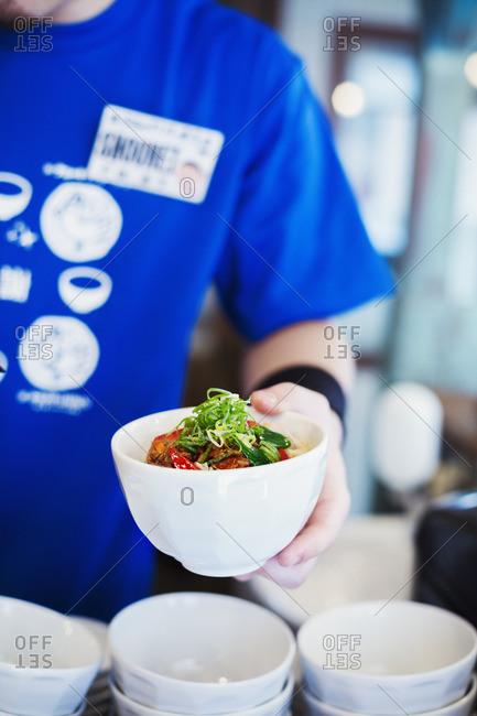 Ramen noodle shop. A chef preparing a bowl of fresh ramen noodles with meat and vegetables.