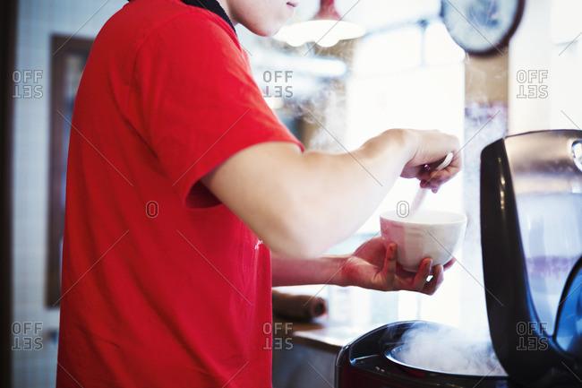 Ramen noodle shop. A man preparing a bowl of noodles.
