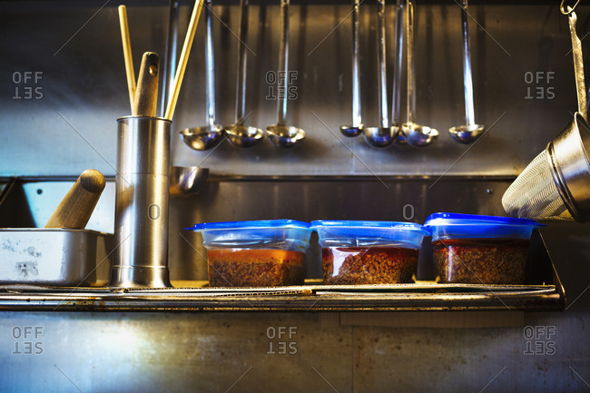 A ramen noodle shop. A kitchen worktop with bowls of fresh cooked  ingredients for ramen dishes. Rows of ladles.