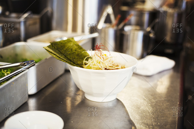 A ramen noodle shop kitchen. A chef preparing bowls of ramen noodles in broth, a speciality and fast food dish.
