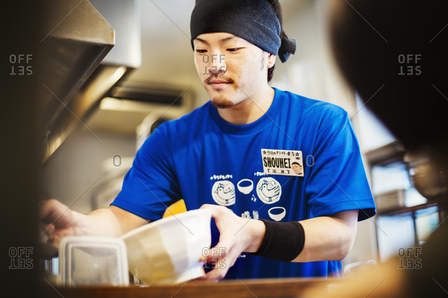 Japan - July 25, 2016: A ramen noodle shop kitchen. A chef preparing bowls of ramen noodles in broth, a speciality and fast food dish.
