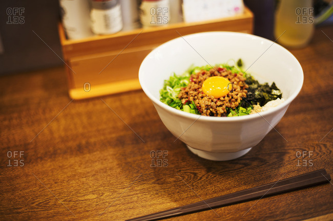 A ramen noodle shop. A white bowl of noodles with vegetables and an egg.