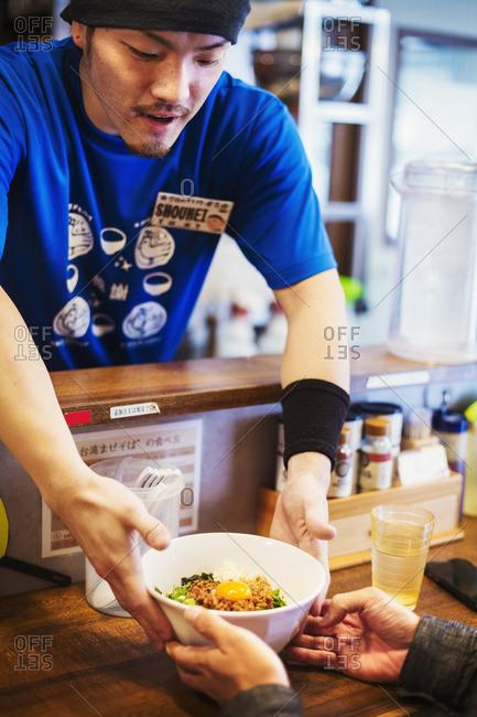 Japan - July 25, 2016: Ramen noodle shop. A chef delivering a bowl of ramen noodles to a customer.