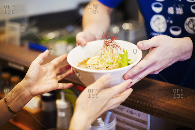 Ramen noodle shop. A chef offering a white bowl of ramen noodle broth to a customer