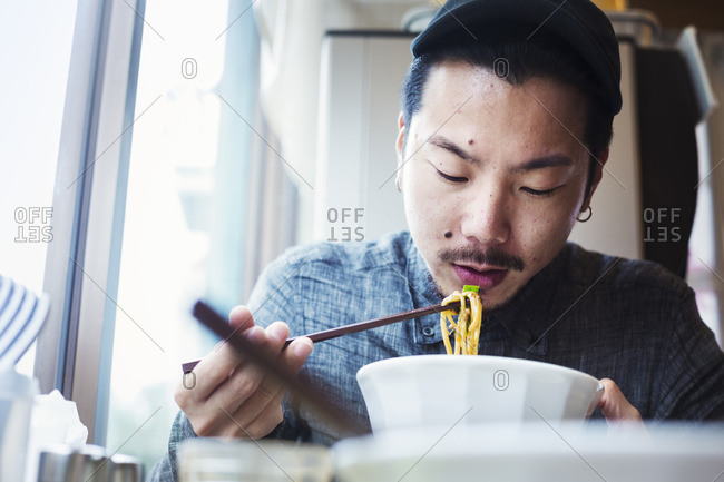 A ramen noodle cafe in a city.  A man sitting eating ramen noodle soup dish.
