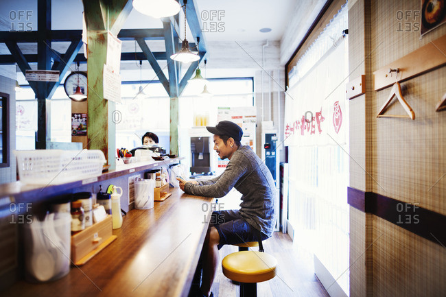 A ramen noodle shop in a city. A man seated at a counter looking at his smart phone.