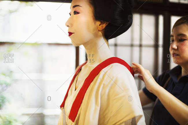 A modern geisha or maiko woman being dressed in traditional fashion in a white shift with loose collar, with white face makeup.
