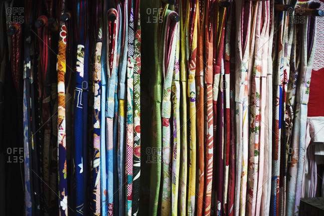 Rows of colorful fabric hanging up, traditional kimonos, a robe with wide sleeves, traditional style.