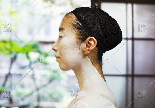A modern geisha or maiko woman in traditional fashion, with white face makeup. Profile.