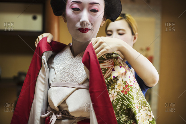 A woman being dressed in the traditional geisha style, wearing a kimono with white face makeup with bright red lips and dark eyes.
