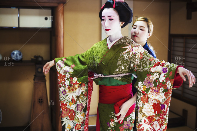 A woman being dressed in the traditional geisha style, wearing a kimono and obi