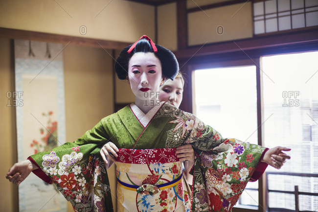 A woman being dressed in the traditional geisha style