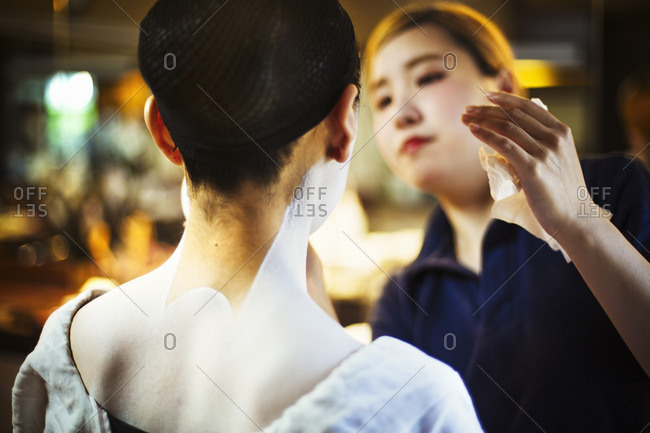 A modern geisha or maiko woman being made up in traditional fashion, with white makeup on her neck and shoulders.
