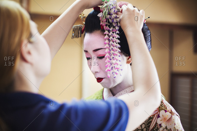A geisha or maiko with a hair and make up artist creating the traditional hair style and make up