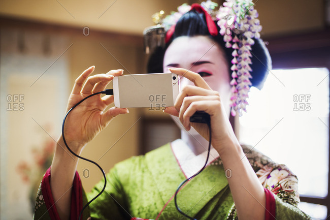A woman dressed in the traditional geisha style, wearing a kimono and obi, taking a selfie