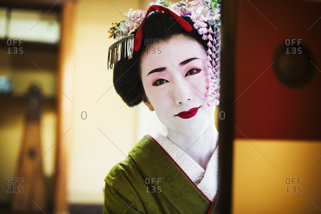 A woman dressed in the traditional geisha style, wearing a kimono and obi, looking in the mirror.