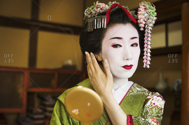 A woman in the traditional geisha style, with an elaborate hairstyle and floral hair clips, looking in a hand mirror