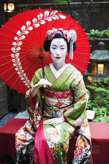 A woman dressed in the traditional geisha style, wearing a kimono and obi