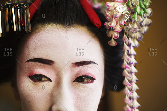 A woman made up in traditional geisha style with an elaborate hairstyle and floral hair clips, drawn eyebrows with white face makeup with bright red lips and outlined eyes.