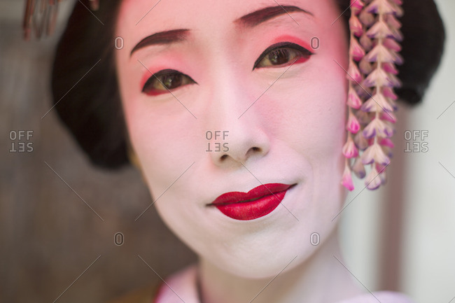 A woman made up in traditional geisha style with an elaborate hairstyle and floral hair clips