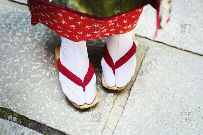 A traditional geisha woman's feet, in wooden soled sandals, with red straps and white stockings or tabi.