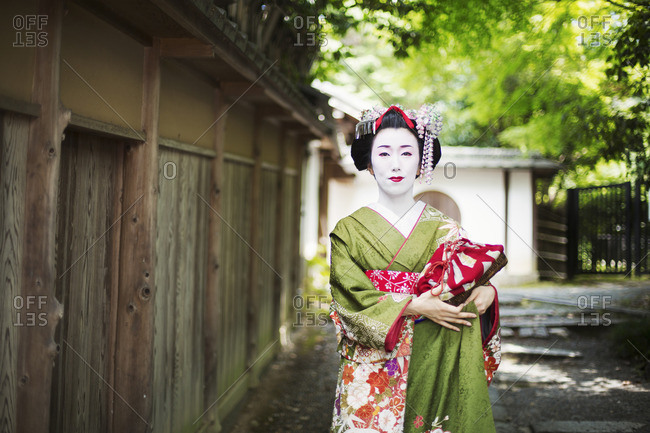 A woman dressed in the traditional geisha style, wearing a kimono and obi on a street