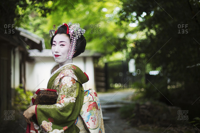 A woman dressed in the traditional geisha style, wearing a kimono and obi, side view outdoors
