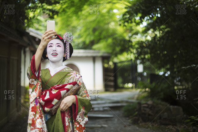 A woman dressed in the traditional geisha style, wearing a kimono and obi taking a selfie