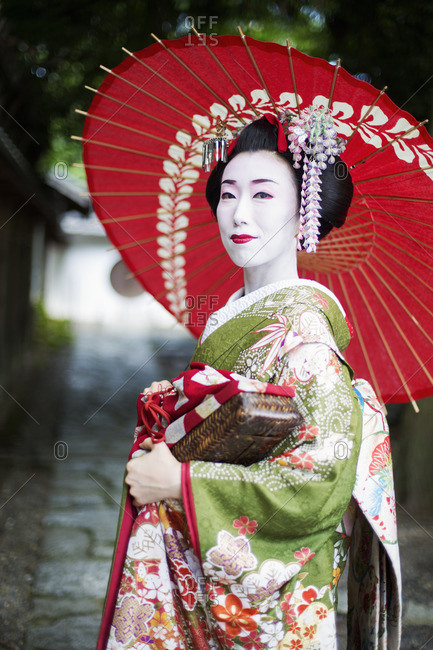 A woman dressed in the traditional geisha style, wearing a kimono and obi holding a red paper parasol