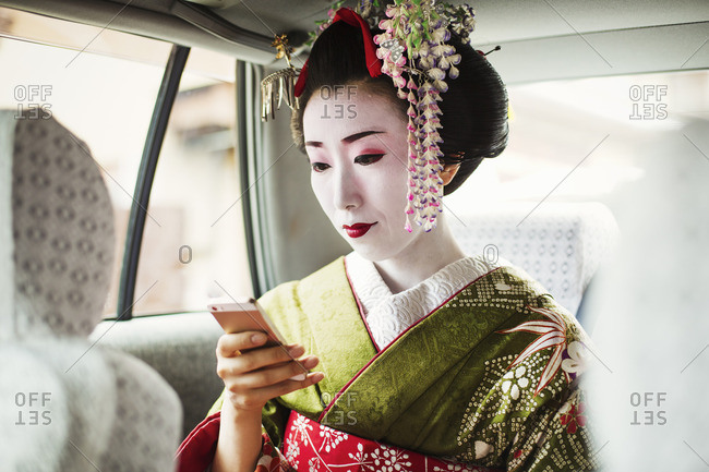 A woman dressed in the traditional geisha style, wearing a kimono and obi in a car using a smart phone