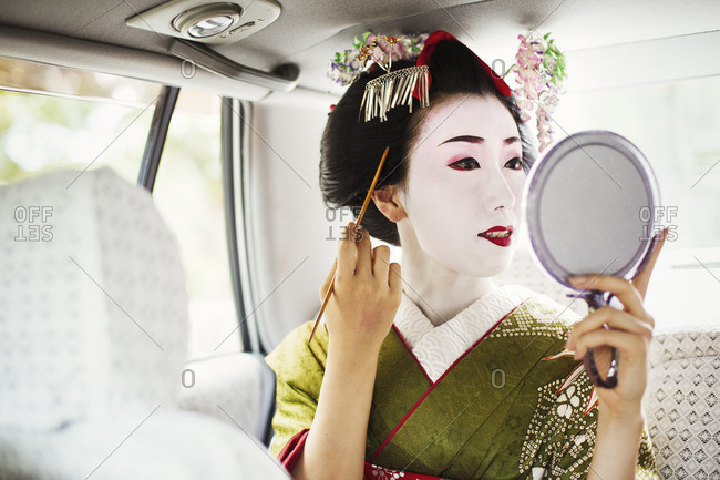 A woman dressed in the traditional geisha style, wearing a kimono and obi in a car using a hand mirror