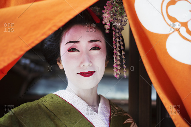 A woman dressed in the traditional geisha style, wearing a kimono with an elaborate hairstyle and floral hair clips