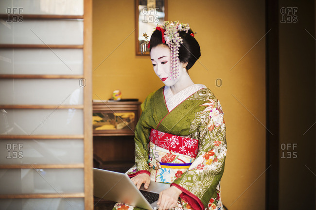 A woman dressed in the traditional geisha style, wearing a kimono and obi using a laptop computer