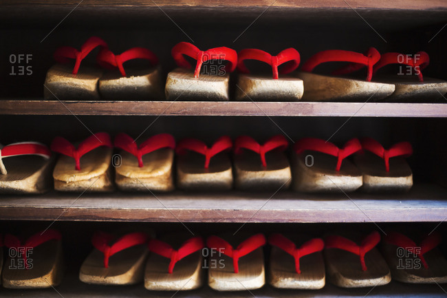 Rows of traditional wooden sandals with thick soles and red straps worn by geisha, okobo or geta