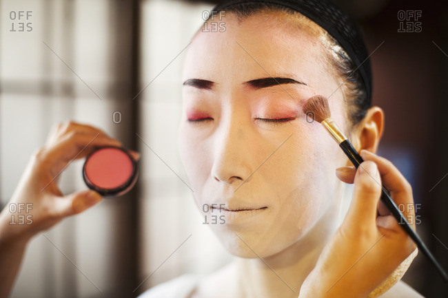 A geisha or maiko with a hair and make up artist creating the traditional hair style and make up using a brush to apply color on her eyelids