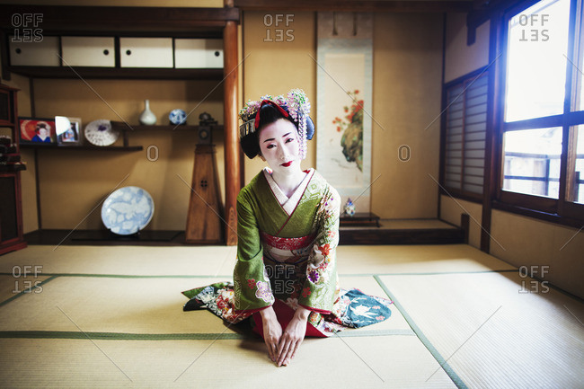 A woman dressed in the traditional geisha style, wearing a kimono and obi with bright red lips and dark eyes, kneeling in a traditional pose.
