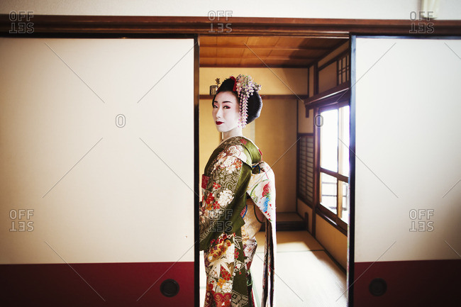 A woman dressed in the traditional geisha style, wearing a kimono and obi with bright red lips and dark eyes