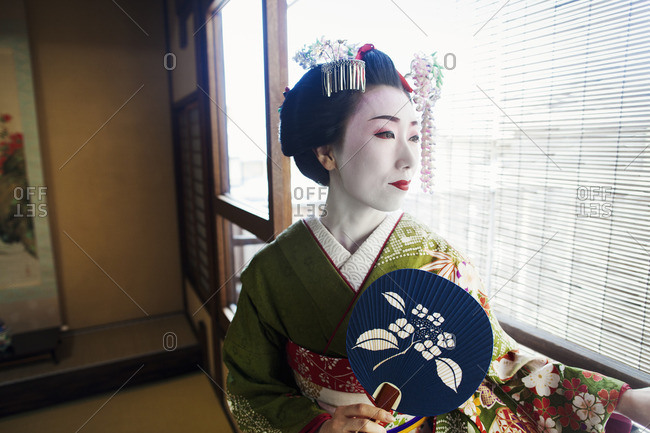A woman dressed in the traditional geisha style, wearing a kimono and obi, holding a fan.
