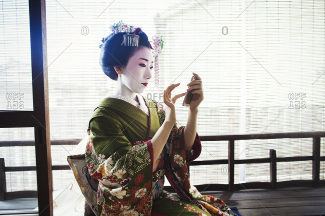 A woman dressed in the traditional geisha style, wearing a kimono and obi with bright red lips and dark eyes taking a selfie of herself.