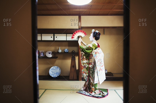 A woman dressed in the traditional geisha style, wearing a kimono and obi holding an open fan up, her kimono arranged on the floor.