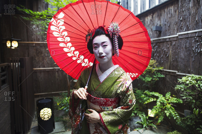 A woman dressed in the traditional geisha style, wearing a kimono and obi with bright red lips and dark eyes holding a red paper parasol.